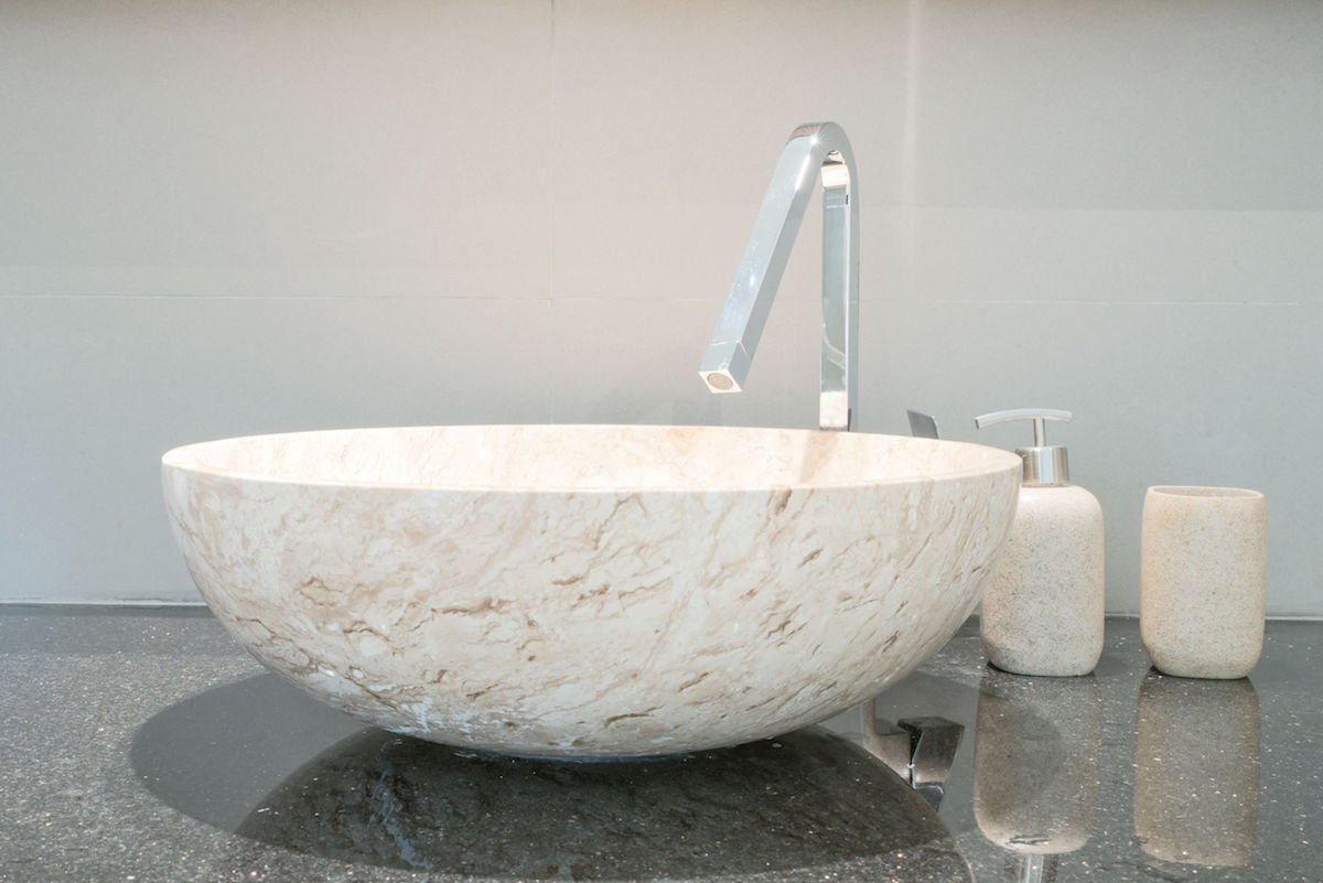 Closeup of a wash basin and silver fixtures in a modern bathroom